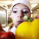 Eine Schülerin die am Berufsorientierungsprogramm des Bundesministeriums für Bildung und Forschung teilnimmt lernt den Beruf des Kochs kennen. Sie steht in einem offenen Kühlschrank und greift nach zwei Paprika.