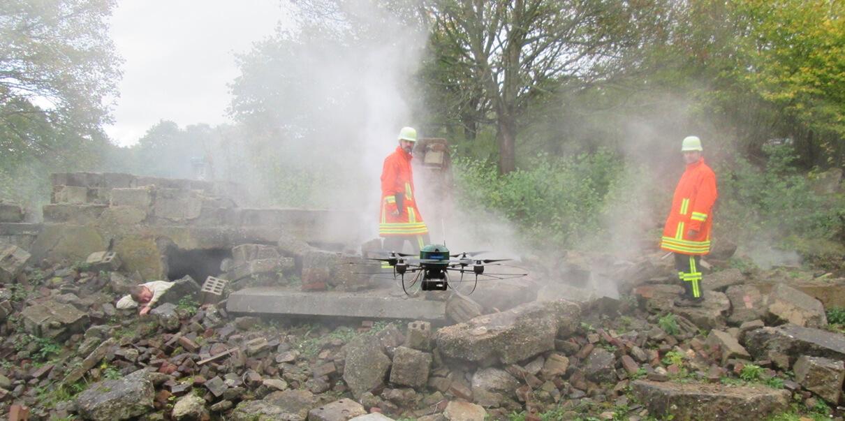 Inmitten eines Trümmerfeldes - eine Drohne die mit einer Kamera bestückt ist schwebt neben zwei Rettungskräften und hilft ihnen bei der Suche nach Verschütteten. Links im Bild liegt ein noch unentdeckter Verwundeter. Screenshot aus einem Projekt der Filmproduktion Karlsruhe mp-film für das Forschungsprojekt Seneka des Fraunhofer Instituts.