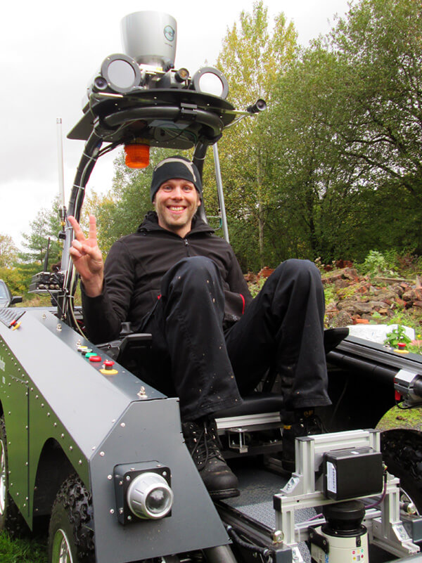 Ein gut gelaunter Wissenschaftler Fraunhofer IOSB in einem autonom fahrenden Fahrzeug komplett ausgerüstet für den Katastrophenfall