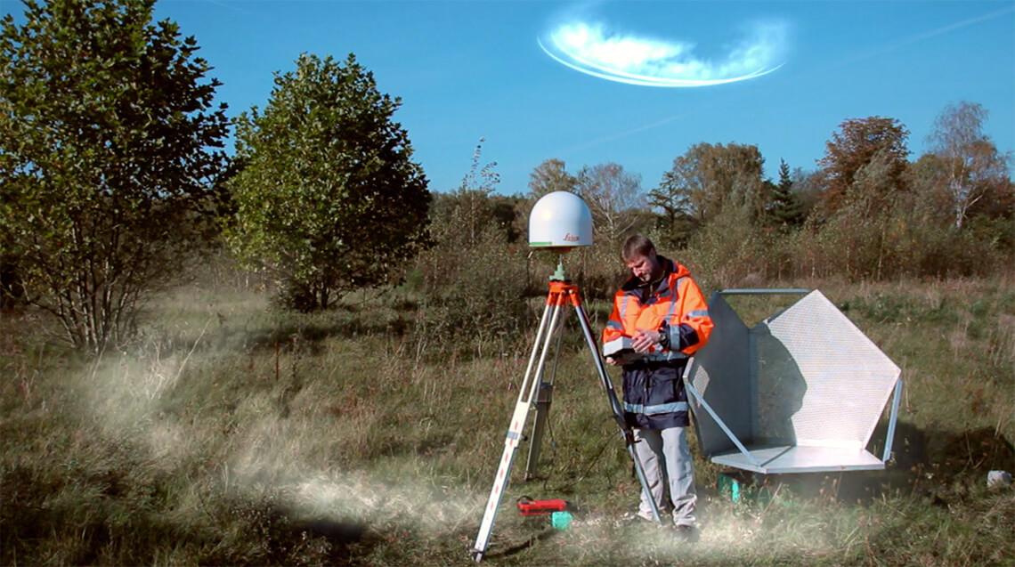 Der Ingenieur der Deutschen Steinkohle AG Volker Sprenkels steht neben einer wissenschaftlichen Versuchsanlage die Erdsenkungen misst. Die Animation zeigt eine Funkwelle die von oben auf die Messstation trifft. Erklärfilm der Filmproduktion Karlsruhe mp-film.