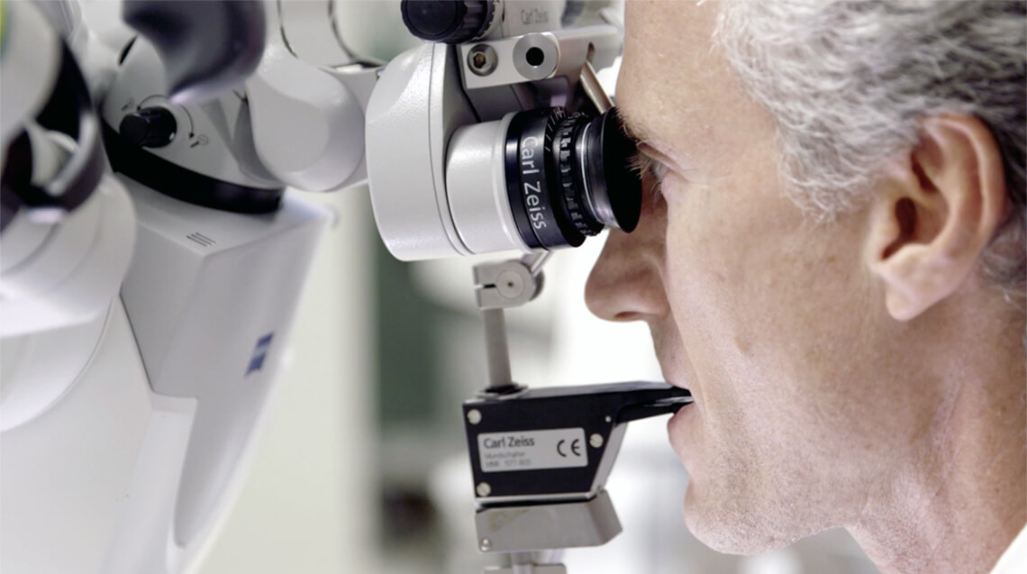 Screenshot aus einem Imagefilm der Filmproduktion Karlsruhe mp-film für die Carl Zeiss AG. Der amerikanische Neurochirurg Prof. Michael Lawton schaut durch ein Operationsmikroskop