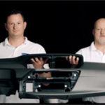 Zwei Mitarbeiter der Faurecia Innenraum Systeme halten ein gemeinsam ein Armaturenbrett in der Hand. Studioaufnahme der mp-film Filmproduktion Karlsruhe