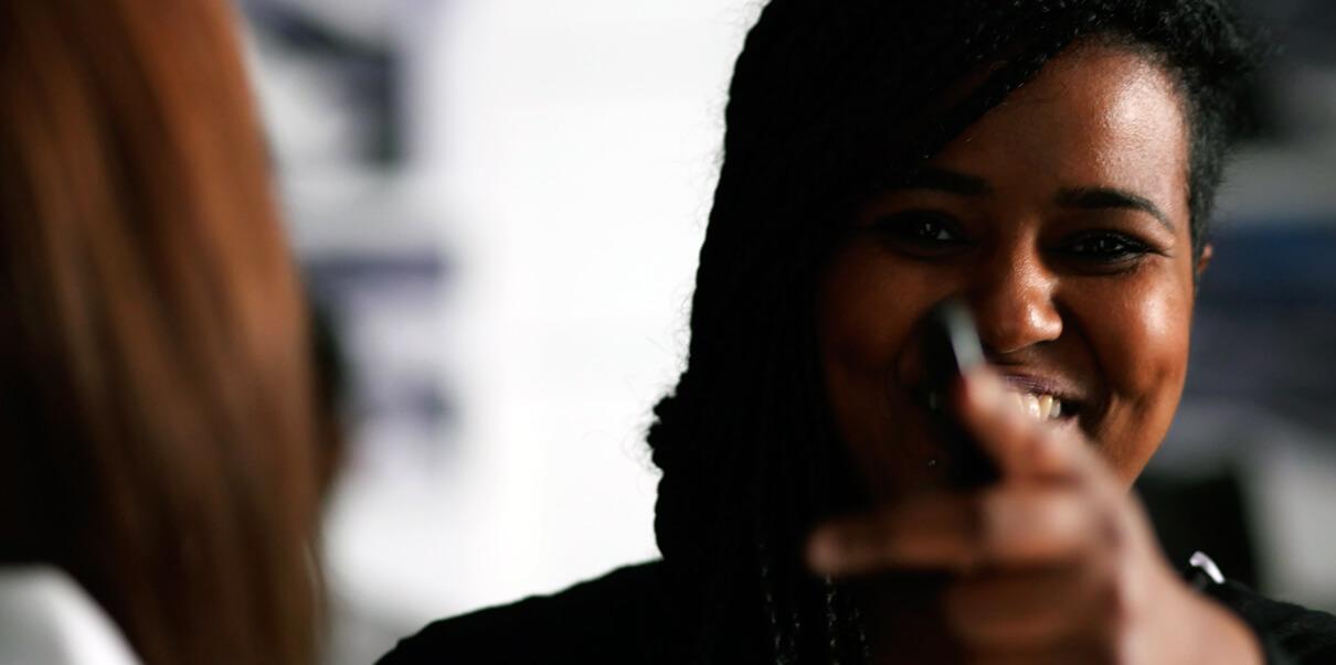 Die Maskenbildnerin der Filmproduktion Karlsruhe mp-film lächelt bei Dreharbeiten für den Visionsfilm der Firma Faurecia Innenraum Systeme