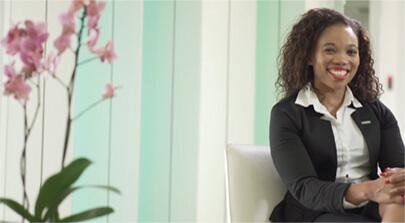 Bild auf der Seite Portfolio. Eine Mitarbeiterin von B. Braun Medizinische Produkte sitzt auf einem Stuhl und lächelt in die Kamera. Imagefilm der Filmproduktion Karlsruhe mp-film für B. Braun