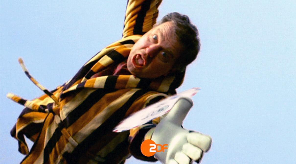 Ein Hausbesitzer im Bademantel hechtet nach einem runden Brief der ihm zwischen den Fingern durchrutscht. Screenshot aus einer Serie Werbespots der Filmproduktion Karlsruhe mp-film für das ZDF.
