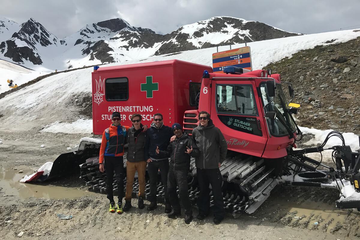 5 Personen des Filmteam der Filmproduktion Karlsruhe mp-film vor einer roten Pistenraupe im Schnee des Stubaier Gletschers in Tirol