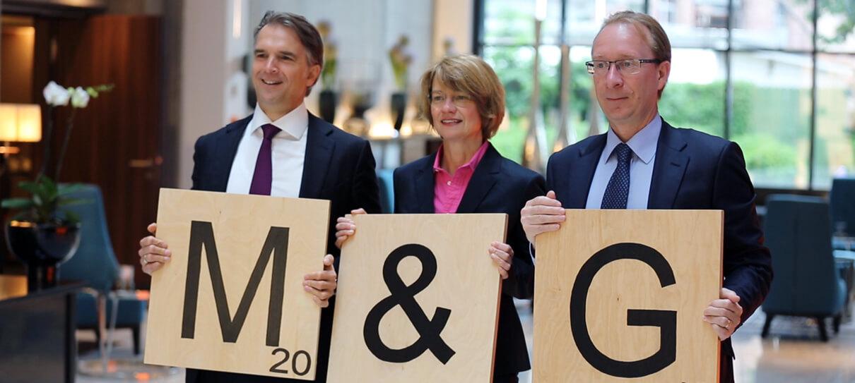 Werner Kolitsch, Richard Woolnough und Sabine Schumann von M&G Investments stehen mit drei Scrabblesteinen in der Hand nebeneinander. Die Buchstaben formen den Firmennamen M&G. Screenshot Eventfilm - Filmproduktion Karlsruhe mp-film für das Unternehmen in Frankfurt von der M&G Jahreskonferenz produziert hat.