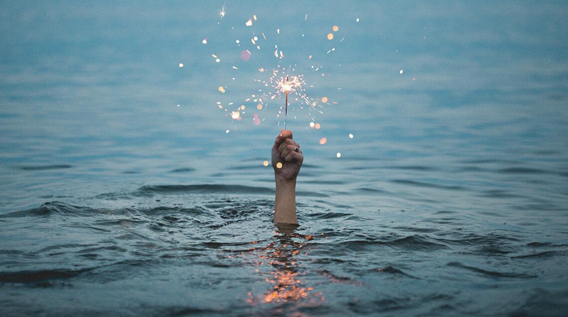 mp-film liefert kreative Lösungen. Eine Hand mit einem Wunderkerze ragt aus den Wasser