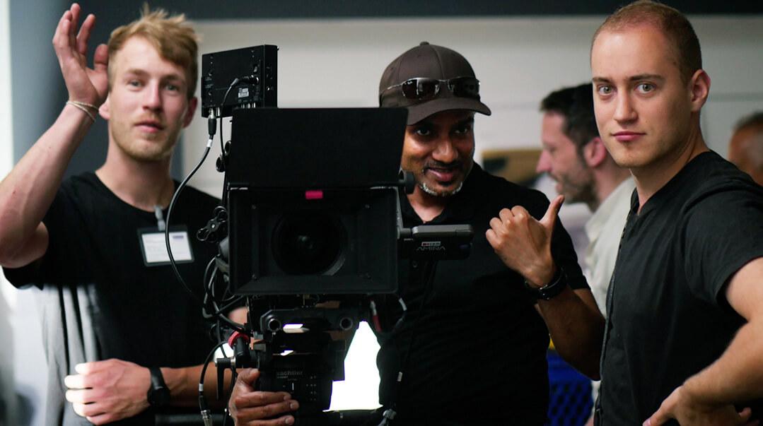 mp-film Team bei Dreharbeiten. Drei Mann neben der Kamera.